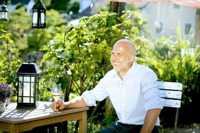 Портрет счастливого человека, сидящего с бокалом белого вина, расслабляющегося в саду — стоковое фото