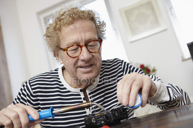 Senior man soldering broken camera — Stock Photo