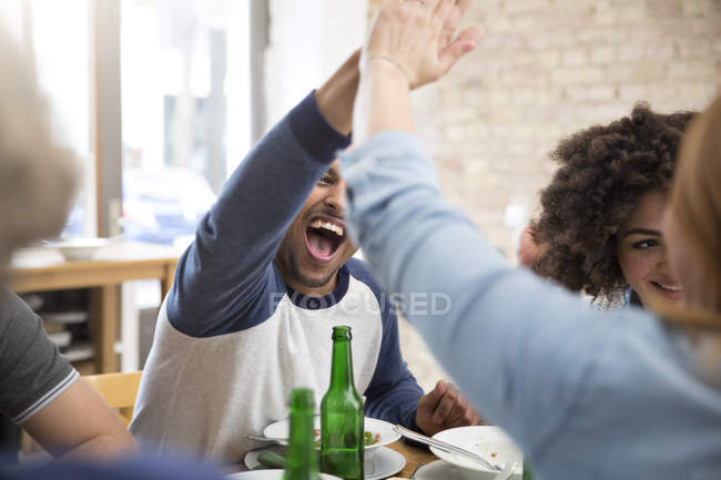 Happy friends at dining table with beer bottles high fiving — Stock Photo