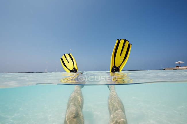 Männliche Füße mit flossen im flachen Wasser auf den Malediven — Stockfoto