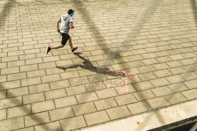 Молодой бегун на дороге в наушниках — стоковое фото
