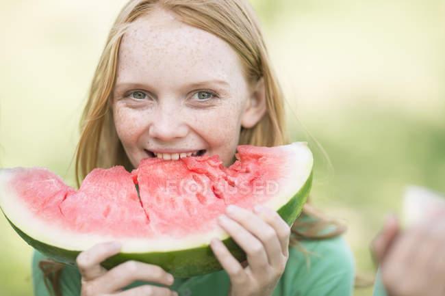 Портрет девушки с рыжими волосами, поедающей ломтик арбуза — стоковое фото