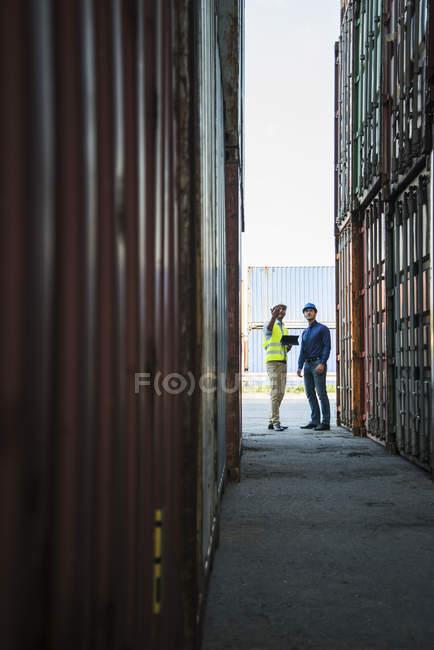 Двоє чоловіків з безпеки касок говорити в порту контейнерів — стокове фото