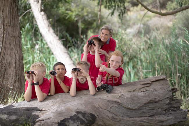 Crianças em viagem de campo, explorar a natureza com binóculos — Fotografia de Stock