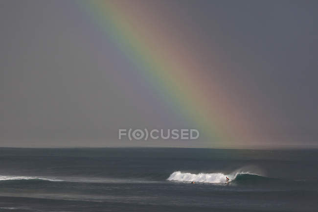 Hombre de Indonesia, Bali, surfeando una ola, arco iris en el cielo - foto de stock