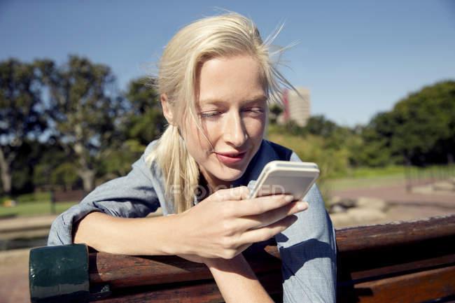 Jovem mulher banco de praça olhando no celular — Fotografia de Stock