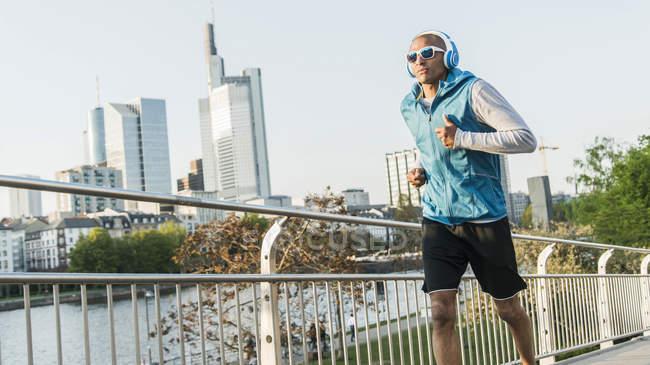 Homme portant un casque jogging sur le pont en ville — Photo de stock