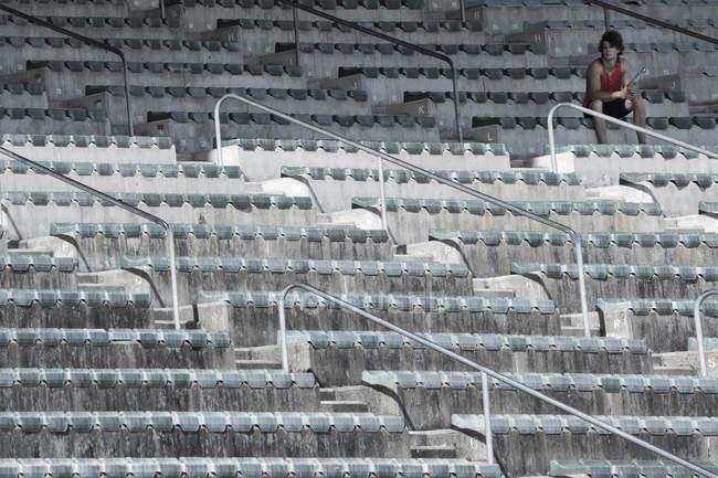 Молодой спортсмен сидит на трибуне стадиона — стоковое фото