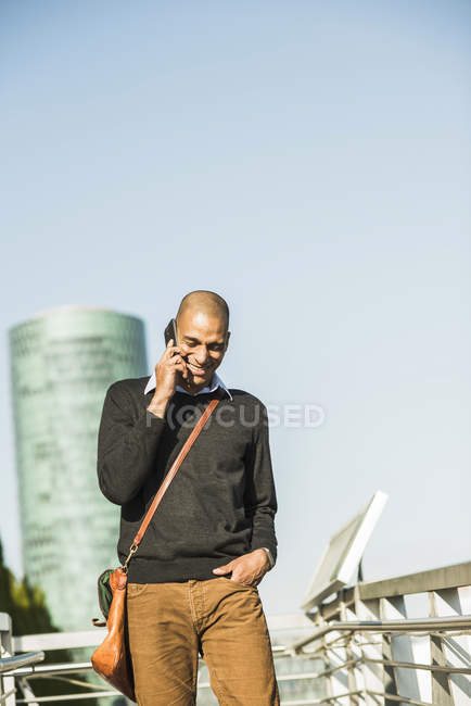 Smiling man outdoors on cell phone — Stock Photo