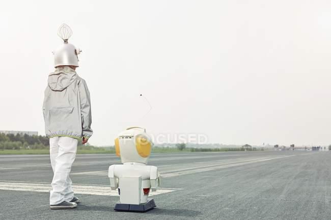 Junge verkleidet sich als Raumfahrer mit Roboter — Stockfoto