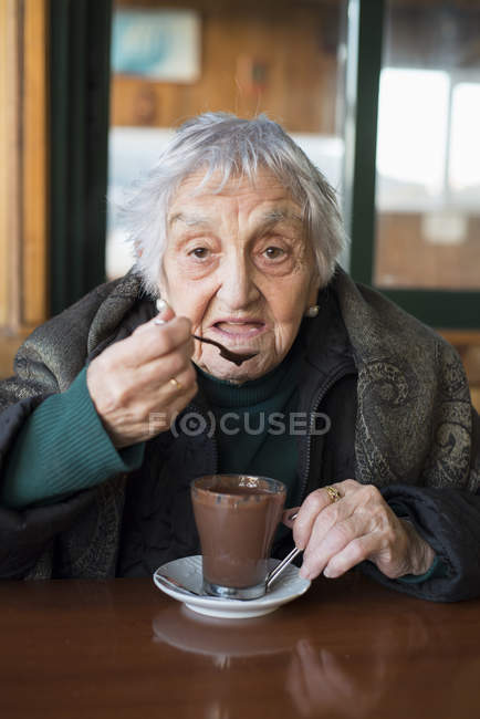 Old woman drinking hot chocolate — Stock Photo