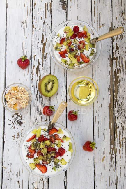 Yogurt kiwi alla fragola con cereali, semi di chia, sciroppo d'agave in ciotole su legno squallido — Foto stock