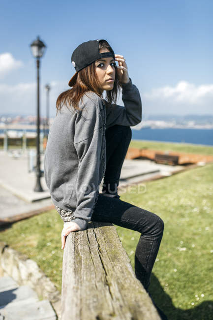 Young woman sitting on wooden beam — Stock Photo
