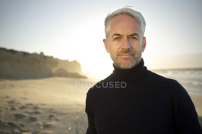Portrait of white haired man wearing turtleneck standing on the beach  before sunrise — Stock Photo