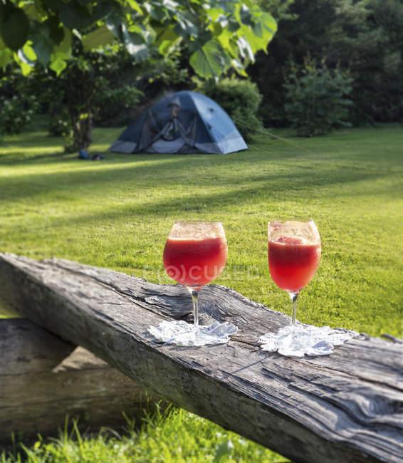 Два асимметричным очки арбуза коктейль на деревянную скамейку — стоковое фото