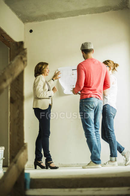 Architect showing construction plan to young couple — Stock Photo