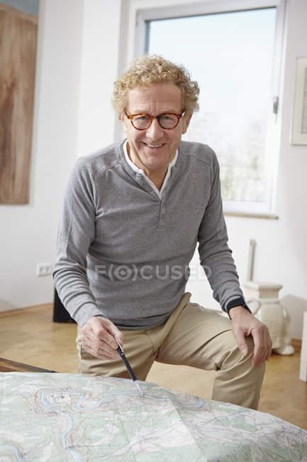 Старший мужчина планирования путешествий, указывая на карте — стоковое фото