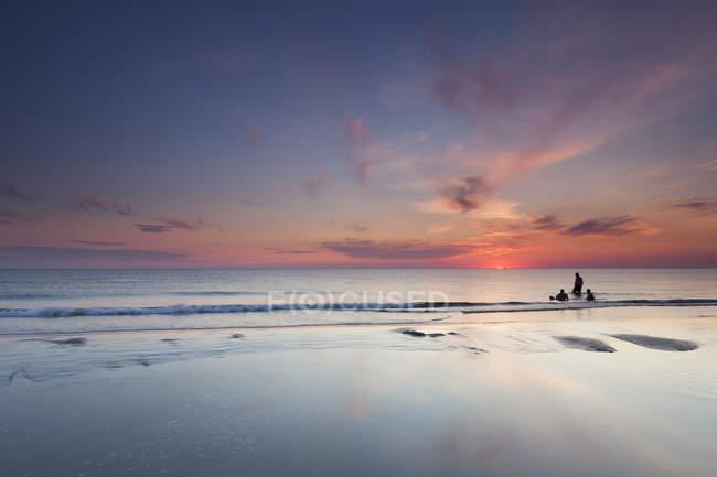 Danemark, Romo, Lakolk, silhouettes de trois personnes de baignade, coucher du soleil — Photo de stock