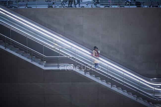 Mujer joven con café para ir de pie en escaleras mecánicas - foto de stock