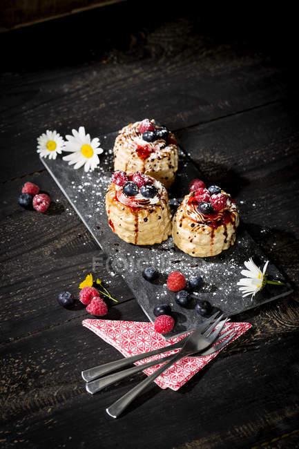 Tartes filo recheadas com sorvete de baunilha e chantilly decorado com mirtilos e framboesas na ardósia — Fotografia de Stock