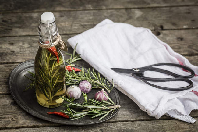 Rosemary oil in bottle, garlic, rosmary and chilli peppers on plate, scissors and kitchen towel on wood — Stock Photo