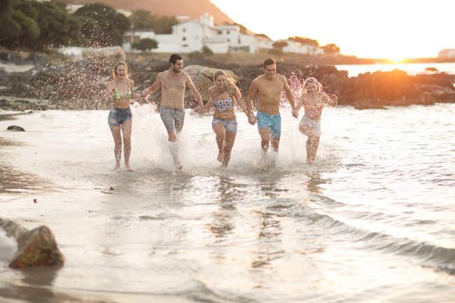 Cinco amigos corriendo en una playa en olas - foto de stock