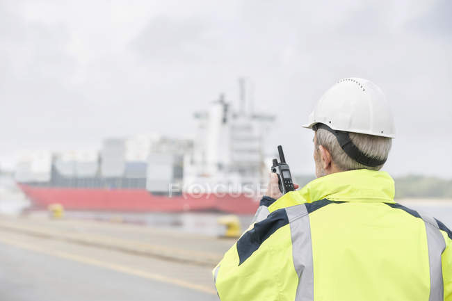 Man with walkie-talkie at container port — Stock Photo