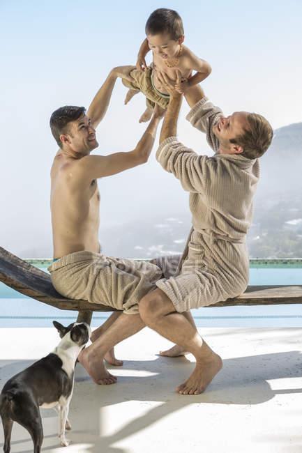 Гей-пара, граючи з дитиною біля басейну — стокове фото