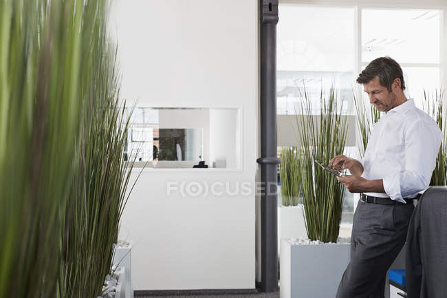 Businessman in office using digital tablet — Stock Photo
