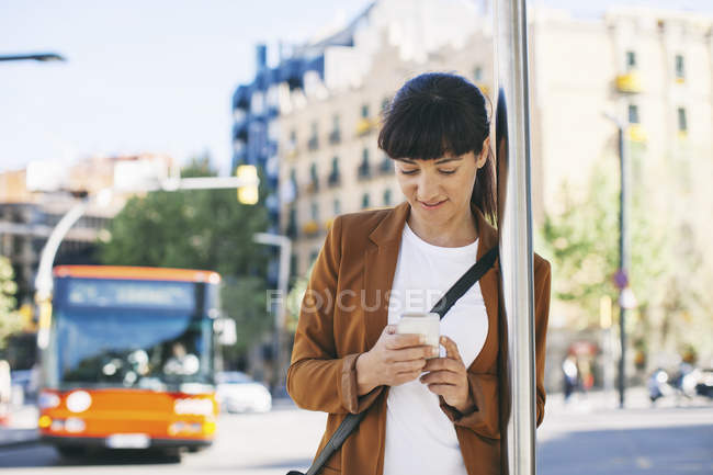 Businesswoman with smartphone waiting at the bus stop — Stock Photo