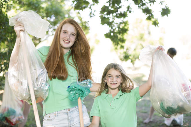 Portrait of two smiling girls showing picked up garbage — Stock Photo