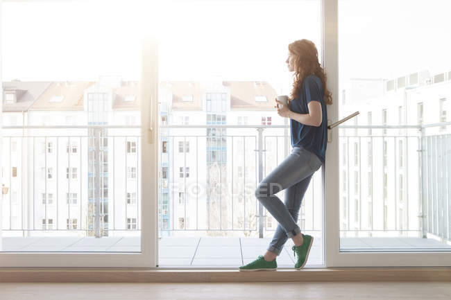 Young woman leaning at sliding door of balcony looking at distance — Stock Photo