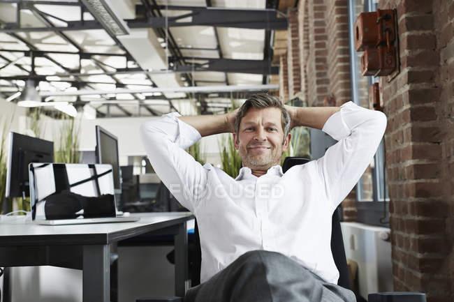 Retrato de homem de negócios sorridente no escritório relaxante — Fotografia de Stock