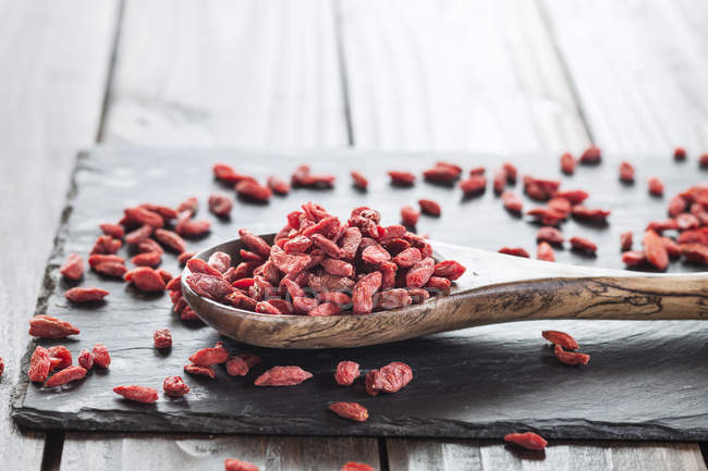 Wooden spoon with goji berries on a slate, superfood — Stock Photo