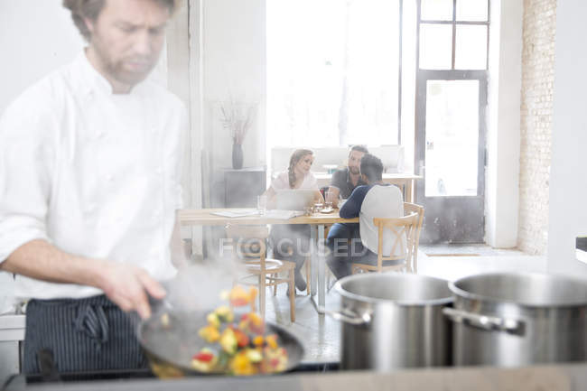 Cook working in kitchen of restaurant while guests communicating on background — Stock Photo