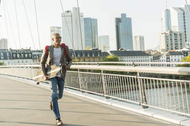 Homme en déplacement portant skateboard et mallette — Photo de stock