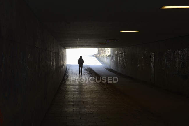Silhouette of man walking in dark tunnel — Stock Photo