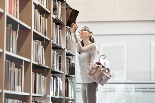 Studente presso prendendo biblioteca Università libro dallo scaffale — Foto stock