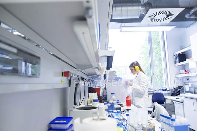 Молодая женщина-ученый работает в биологической лаборатории с помощью ультразвукового аппарата — стоковое фото