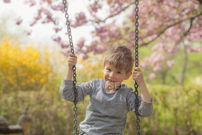 Cherry blossom, Little boy sitting on swing, smiling — Stock Photo