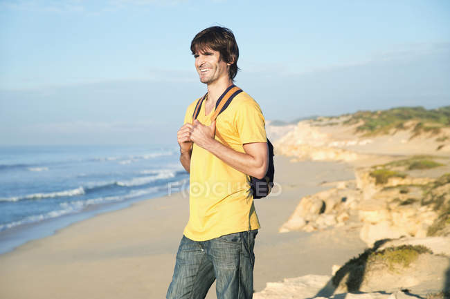 Smiling man standing at the coast — Stock Photo
