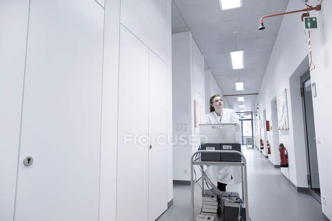 Jeune femme scientifique travaillant au laboratoire biologique poussant chariot — Photo de stock