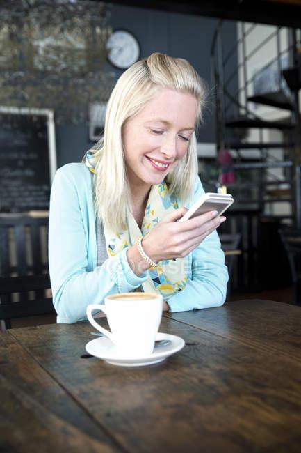 Giovane donna in un caffè guardando sul cellulare — Foto stock