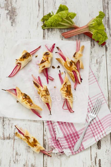 Ревінь у листкове тісто з мигдалю стрічках на папір і кухонне рушник — стокове фото