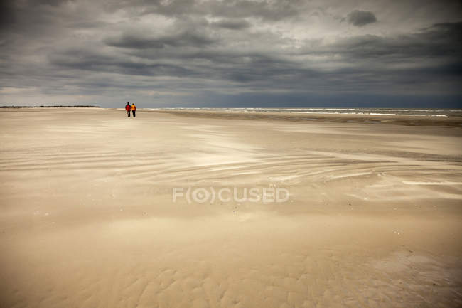 Casal tendo a pé na maré baixa — Fotografia de Stock