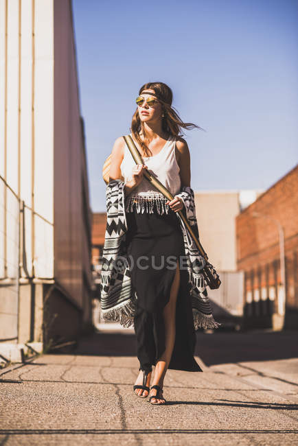 Young woman wearing boho style walking on street — Stock Photo