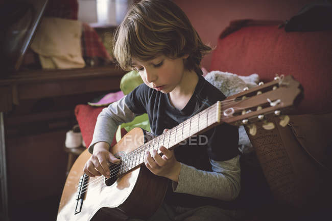 Little boy playing acoustic guitar at home — Stock Photo