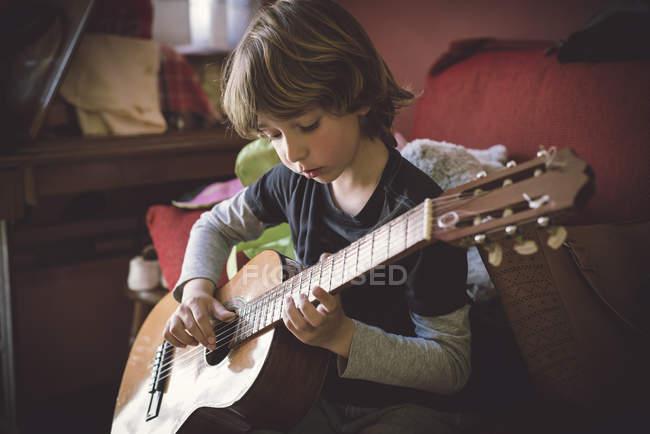 Kleiner Junge spielt zu Hause Akustikgitarre — Stockfoto