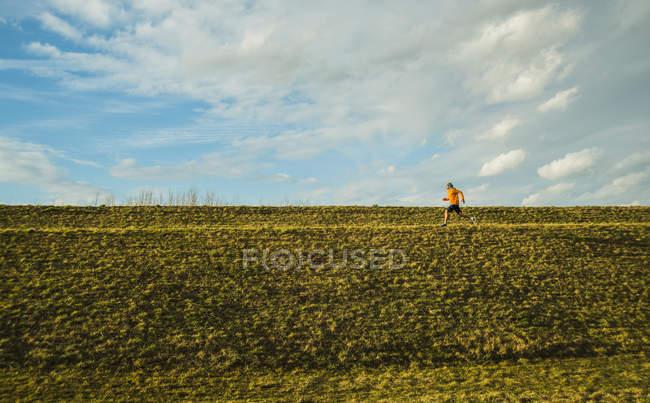 Jovem homem correndo no prado — Fotografia de Stock