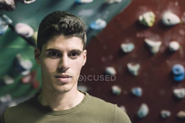Portrait of young man in front of climbing wall — Stock Photo